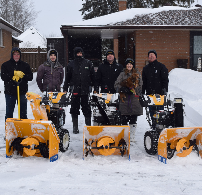 group posting in front of snow blowers